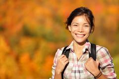 Asian woman hiker hiking in Autumn forest - stock photo