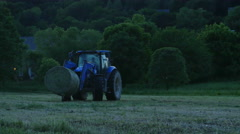 3615 Tractor Moving Bales of Hay Cut at Sunset, 4K Stock Footage