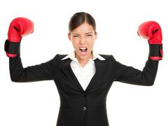 Boxing gloves business woman angry - concept showing aggressive businessperson - stock photo