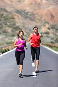 Running couple - Two runners training for marathon run Stock Photos