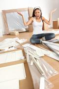 Woman moving in - furniture assembly frustration Stock Photos
