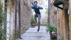 Very happy man runs and jumps in the street : slow motion footage Stock Footage