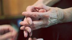 Young arms take care of the hands of elderly woman Stock Footage