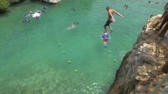 Jumping off the cliff into the water at Xel-ha park, Mexico - stock footage