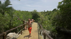 Walking on the wooden bridge at Xel-Ha Park in Mexico - stock footage