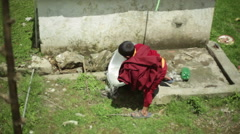 Young buddhist monk boy washing dishes, long shot Stock Footage