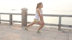 asian girl stretches legs on embankment at dawn - stock footage