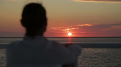 Man looking at the horizon in the sunset - stock footage