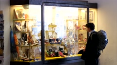 A tourist looks at souvenirs in a shop window in Vienna Stock Footage