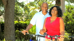 Healthy outdoor cycling exercise retired African American couple male female Stock Footage