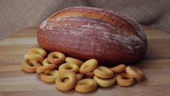 French bread and bagels beautifully rotate on a wooden background Stock Footage