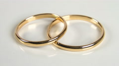 Two golden wedding rings on white background closeup rotation 4K Stock Footage