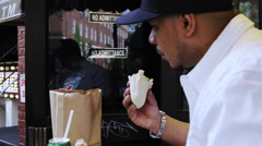 Latino man eating felafel at famous Mamoun's restaurant in slow motion 4K NYC Stock Footage