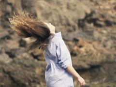 Young woman in shirt throwing her hair  standing on rocks sea,slow motion NTSC Stock Footage