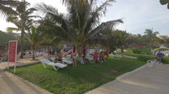 Tourists relaxing under a palm tree at Grand Oasis Cancun Stock Footage