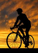 cyclist riding a road bike at sunset  Stock Photos