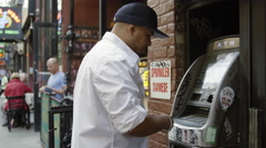 Hispanic man with hat making withdrawal ATM cash machine slow motion 4K NYC Stock Footage