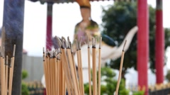 Smouldering incense sticks close up, against blurred Buddha statue Stock Footage