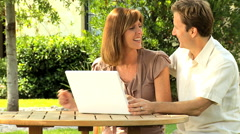 Lifestyle leisure wireless laptop computer male female Caucasian couple outdoor Stock Footage