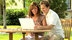 Caucasian US male female couple outdoors wifi wireless laptop computer device Stock Footage