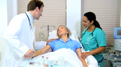 Hispanic nurse clinical Caucasian male hospital doctor female senior patient Stock Footage