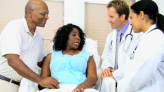 Caucasian male doctor female African American senior patient clinical healthcare Stock Footage