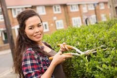 young woman cutting her hedge - stock photo