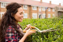 Stock Photo of young woman cutting her hedge