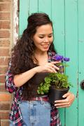 young woman holding a flower pot in the garden - stock photo