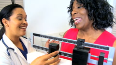 African American senior female Hispanic doctor weighing scales healthcare weight Stock Footage