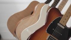 Focus Shifting through various guitars on an instrument rack Stock Footage
