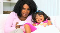 Infant African American female child girl mother playing fun games console Stock Footage