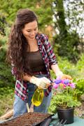 young woman spraying pesticide on her flowers. - stock photo