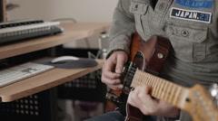 Medium closeup of man playing fender electric guitar - focus shifting Stock Footage