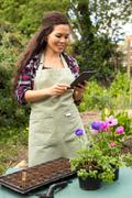 young woman in the garden looking at her tablet for gardening instructions. - stock photo