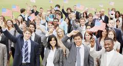 Portrait of smiling business people waving American flags overhead - stock photo