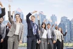 Portrait of smiling business people waving American flags - stock photo
