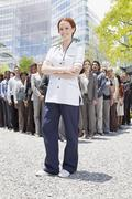 Portrait of confident nurse with business people in background Stock Photos