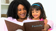 Female ethnic mother young daughter child togetherness home indoors photo album Stock Footage