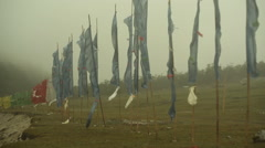 Colorful Buddhist prayer flags blowing in strong wind, Medium shot, pan left Stock Footage
