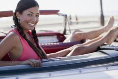 Smiling woman relaxing in convertible - stock photo