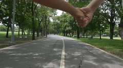 Happy Asian child and mother running along the road in the park, slow motion Stock Footage