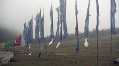 Buddhist prayer flags blowing in strong wind, Medium shot, pan left Stock Footage