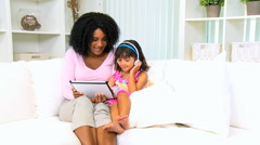 Infant African American female child girl loving mother playing fun tablet Stock Footage