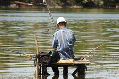 fisherman on the bridge - stock photo