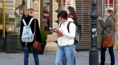Woman tourist in Vienna walks flipping through the guide and map of the city Stock Footage