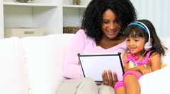 Young African American mother female pre school child playing tablet together Stock Footage