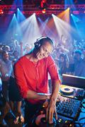 DJ at turntable with crowd on dance floor in background - stock photo