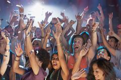 Enthusiastic crowd cheering at concert Stock Photos
