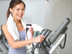 Gym woman fitness workout - girl exercising on moonwalker treadmill gym Stock Photos